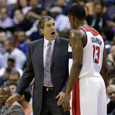 Washington coach Randy Wittman and forward Kevin Seraphin have a discussion against Miami. Photo: Alex Brandon / Associated Press