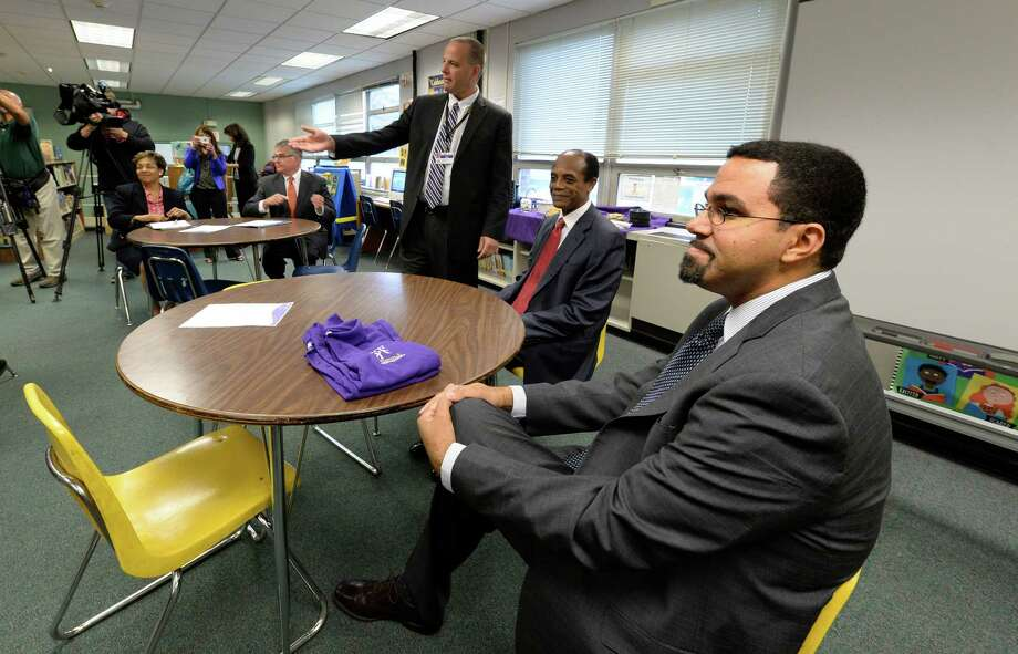 Commissioner of Education John B. King Jr. listens to a presentation by Troy schools superintendent John Carmello, left, at Troy Public School 2 Tuesday morning, Oct. 15, 2013, in Troy, N.Y.  King is joined by Regent James Jackson, center.   (Skip Dickstein/Times Union) Photo: SKIP DICKSTEIN / 00024249A