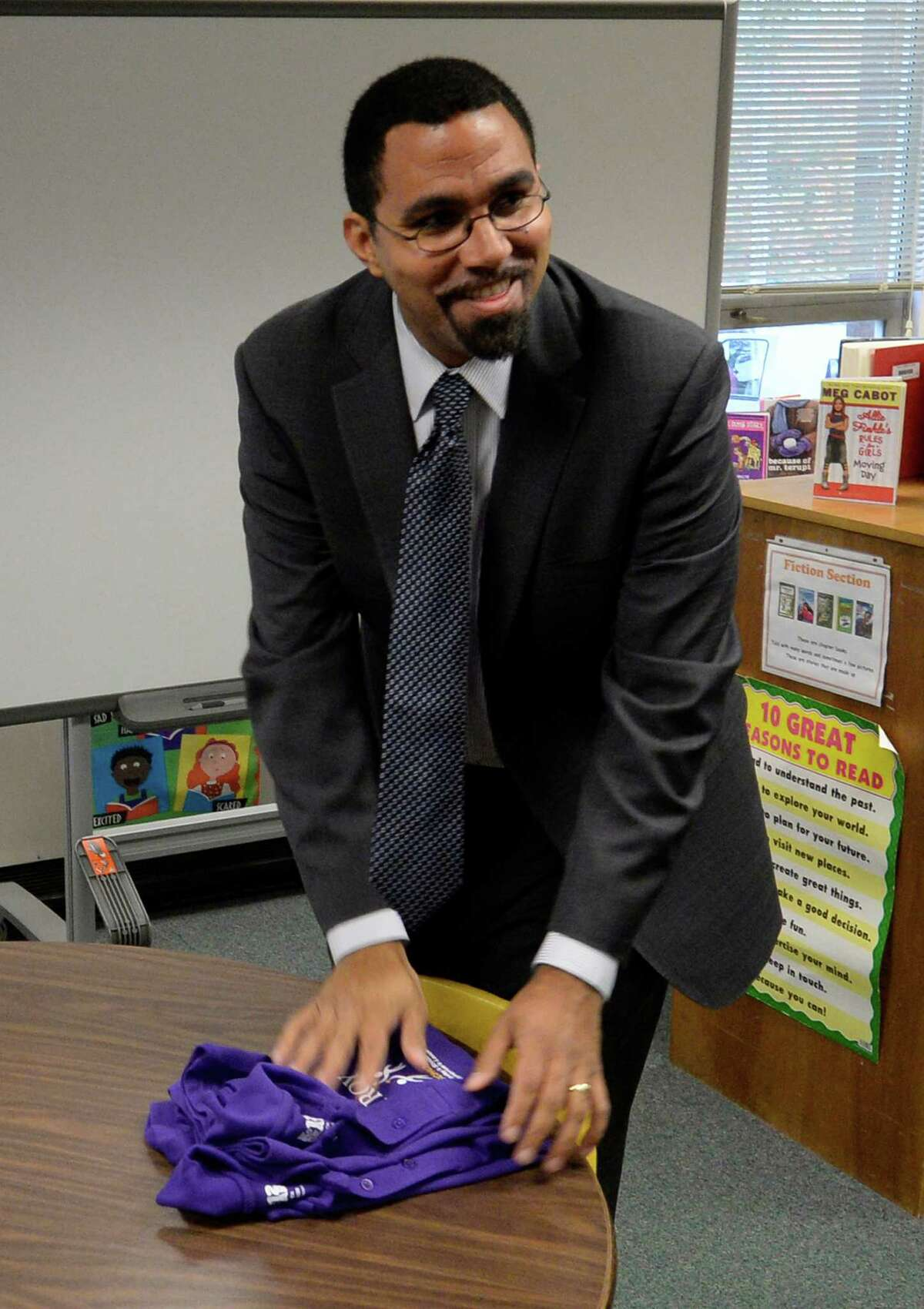 Commissioner of Education John B. King Jr. gathers up some shirts at Public School 2 Tuesday morning, Oct. 15, 2013, in Troy, N.Y. (Skip Dickstein/Times Union)