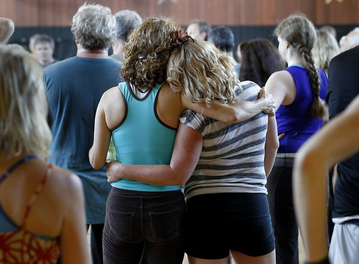 Two women held each other as they listened to words spoken in between the music Sunday September 15, 2013 in Sausalito, Calif. A weekly event called