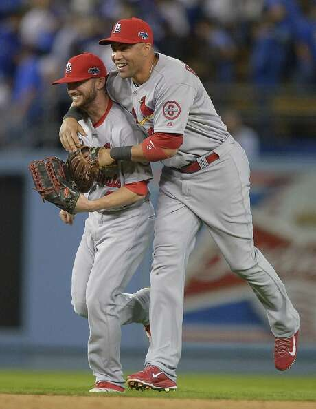 Shane Robinson (left), who had a solo home run in the seventh inning, and Carlos Beltran celebrate after the Cardinals took a 3-1 lead in the NLCS. Photo: Mark J. Terrill / Associated Press