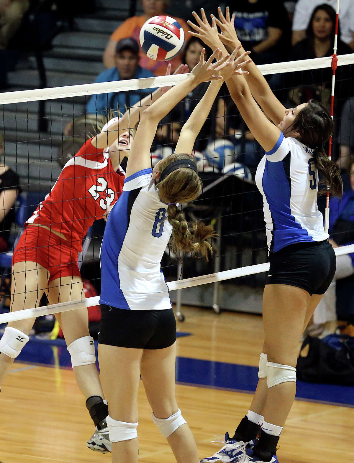 Canyon's KK Payne hits the ball into Alexis Uleman (8) and Avery Rios as New Braunfels hosts Canyon in volleyball at New Braunfels High School gym on October 15, 2013.