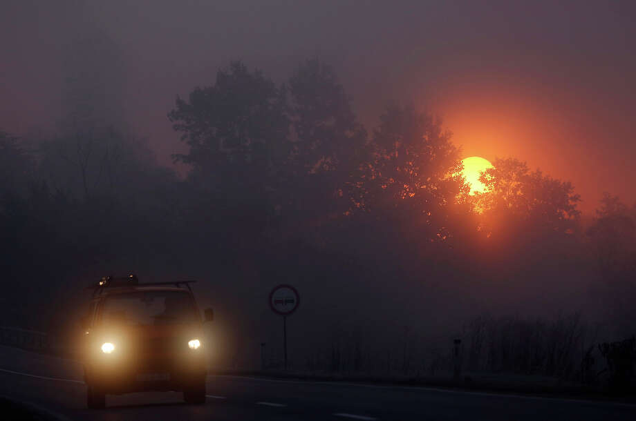 A passengers car drives along a foggy road as the sun rises near Sarajevo, Bosnia, Monday, Oct. 14, 2013. Morning fog is a regular occurrence in the Sarajevo valley, particularly during the cooler months of autumn. Photo: Amel Emric, ASSOCIATED PRESS / AP2013