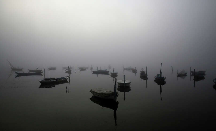 Fog obscures the lagoon of Messolongi, in western Greece, on Monday Oct 14, 2013, as fishing boats are anchored along the boardwalk. Autumn fogs are a common occurrence in this part of the country. Photo: Dimitri Messinis, ASSOCIATED PRESS / AP2013