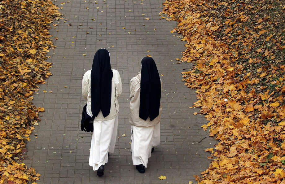 Catholic nuns walk in a park among seasonal colored trees on an autumn day in the Belarusian capital of Minsk, Monday, Oct. 14, 2013. (AP Photo/Sergei Grits) Photo: Sergei Grits, ASSOCIATED PRESS / AP2013