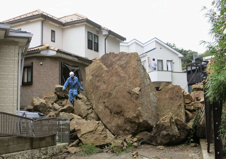 A fire fighter walks over rocks fallen from a cliff over a garage and a road in a residential area in Kamakura, southwest of Tokyo, after a powerful typhoon hit Japan's metropolitan area Wednesday morning, Oct. 16, 2013. Typhoon Wipha triggered landslides and caused multiple deaths on a Japanese island off Tokyo, before sweeping up the country's east coast, grounding hundreds of flights and paralyzing public transportation in Tokyo during Wednesday morning's rush hour. Photo: Uncredited, ASSOCIATED PRESS / AP2013