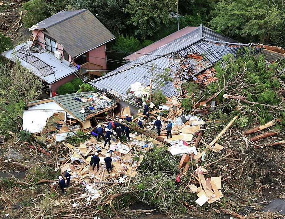 Rescue workers look for survivors as they stand on the rubble of a house buried by mudslides after a powerful typhoon hit Oshima on Izu Oshima island, about 120 kilometers (75 miles) south of Tokyo Wednesday morning, Oct. 16, 2013. Typhoon Wipha has lashed Japan, leaving at least seven people dead on a Pacific island south of Tokyo as it cut across the capital region and headed north. Photo: Uncredited, ASSOCIATED PRESS / AP2013