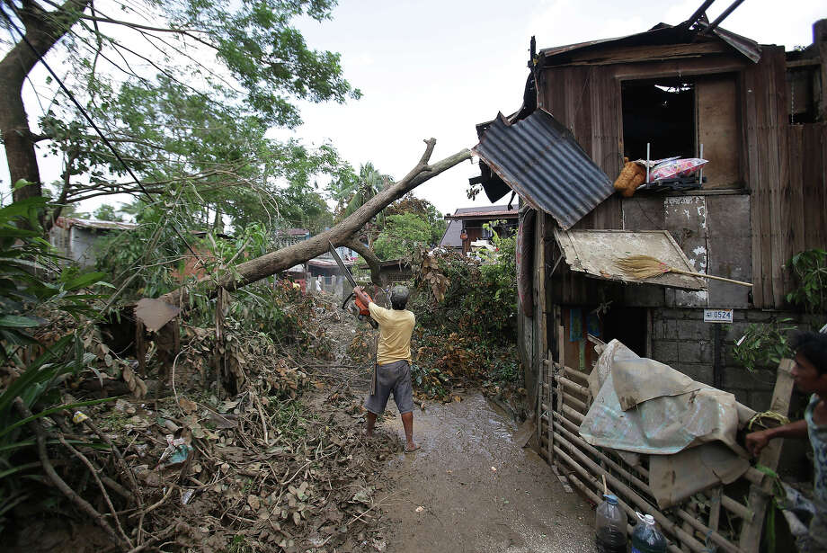 A Filipino uses a chainsaw to cut toppled trees after typhoon Nari hit San Miguel town, Bulacan province, northern Philippines on Sunday, Oct. 13, 2013. The typhoon flooded villages and farms in the Philippines' major rice-growing region and has killed at least 13 people, officials said. Photo: Aaron Favila, ASSOCIATED PRESS / AP2013
