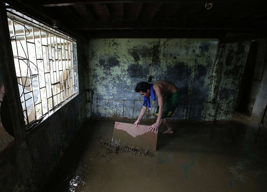 A resident cleans out mud inside his house after typhoon Nari hit San Miguel town, Bulacan province, northern Philippines on Sunday, Oct. 13, 2013. The typhoon flooded villages and farms in the Philippines' major rice-growing region and has killed at least 13 people, officials said. Photo: Aaron Favila, ASSOCIATED PRESS / AP2013