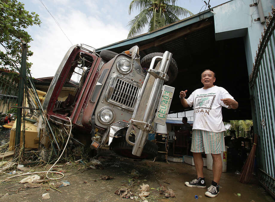 Ed Mangaluz, 78, gestures as he tells his story on how his jeepney got washed away by strong currents during the height of floods caused by Typhoon Nari at San Miguel town, Bulacan province, northern Philippines on Sunday, Oct. 13, 2013. The typhoon flooded villages and farms in the Philippines' major rice-growing region and has killed at least a dozen people, officials said. Photo: Aaron Favila, ASSOCIATED PRESS / AP2013