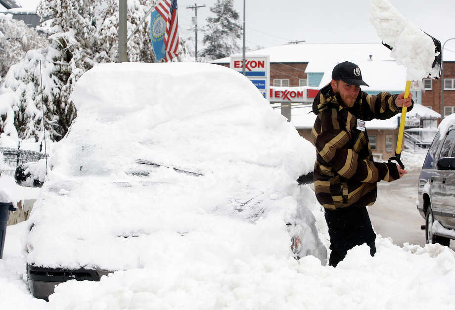 Joey Canida shovels snow away from his van on Main Street in Lead, S.D., Tuesday morning, Oct. 15, 2013, so he can get to work. Photo: Chris Huber, AP / Rapid City Journal