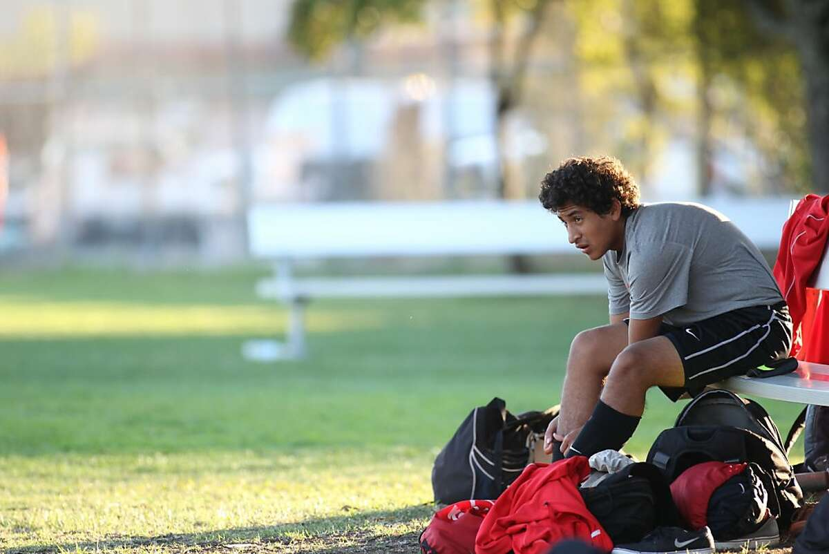 Alex Argueta puts on shin guards during practice at San Rafael High in San Rafael, Calif. on Tuesday, Oct. 15, 2013.