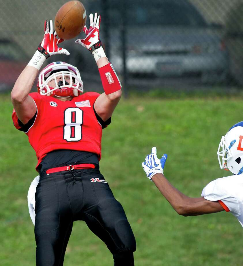 New Canaan's Robby Paul leans back to catch a pass for a touchdown during Saturday's football game at New Canaan High School on October 12, 2013. Photo: Lindsay Perry / Stamford Advocate