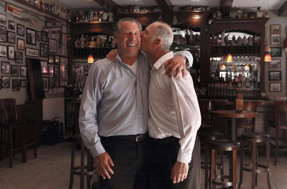 Owner Paul Capurro kissed by his brother and daytime floor manager Frank Capurro at Capurro's in San Francisco. Photo: Liz Hafalia, The Chronicle
