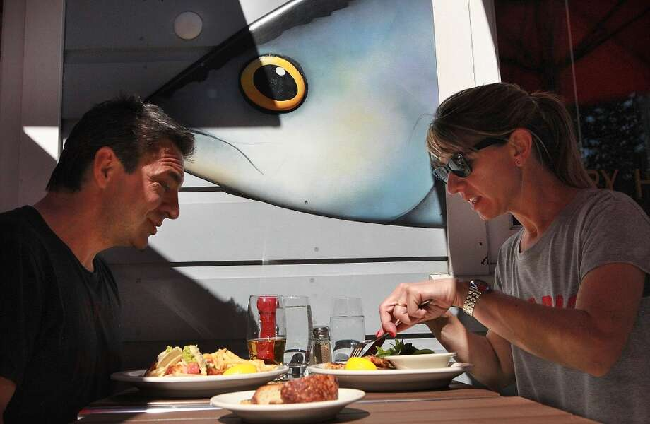 Joaquin Anderson (left) and Maru Anderson (right) visiting from Argentina have lunch in front of Capurro's in San Francisco. Photo: Liz Hafalia, The Chronicle