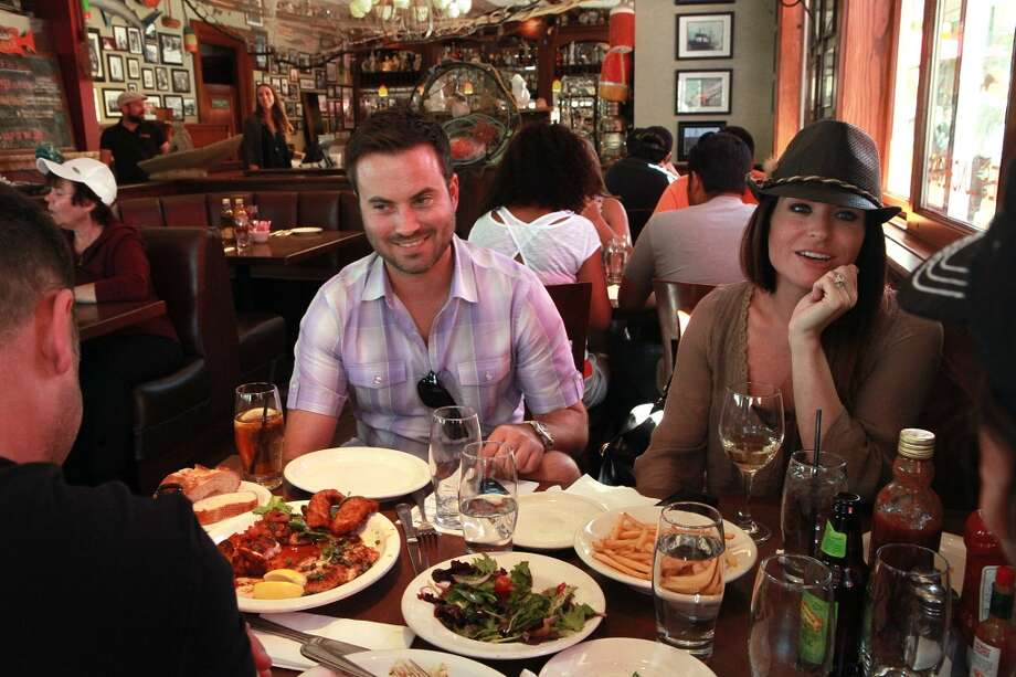 Shon Hill (left) and Nicholette Brown (right) visiting from Texas talk with Jason Freeman (far left) and Christian Natoli (far right) from New York, a couple they just met at Capurro's in San Francisco. Photo: Liz Hafalia, The Chronicle