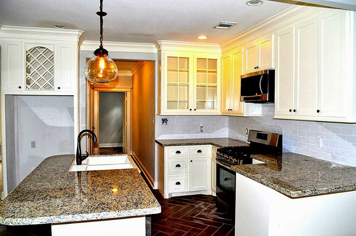 A custom island kitchen holds recessed lighting and ample amounts of cabinetry.