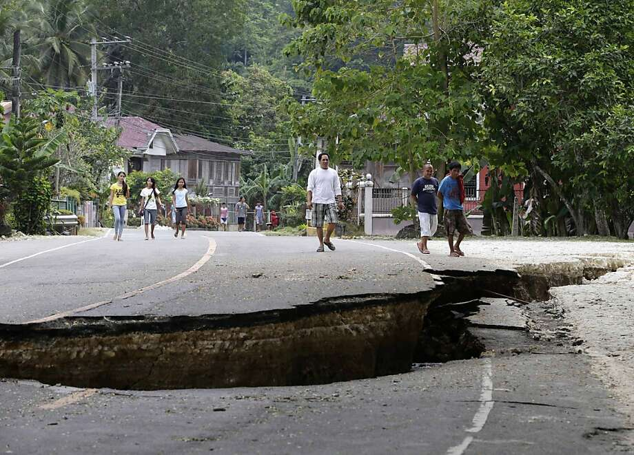 Fault finders:Filipinos examine damaged roadway in Loboc township after a 7.2-magnitude quake hit Bohol and   Cebu provinces. The tremor collapsed buildings, cracked roads and toppled the bell tower of the Philippines'   oldest church. At least 144 people died. Photo: Bullit Marquez, Associated Press