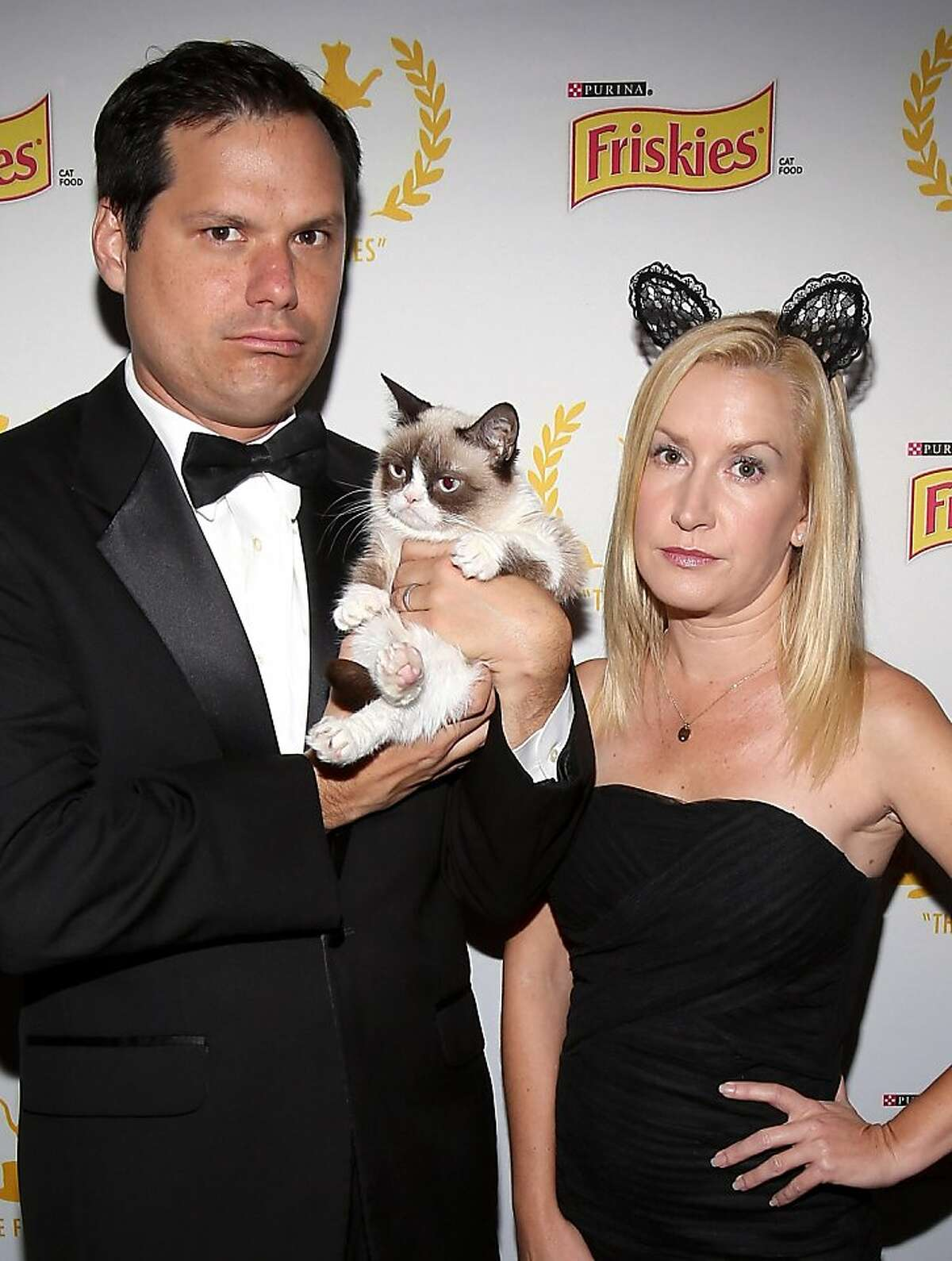Did I shed on you? Good! At Friskies 2013, Grumpy Cat's mood rubs off on actors Michael Ian Black and Angela Kinsey. As does her fur.