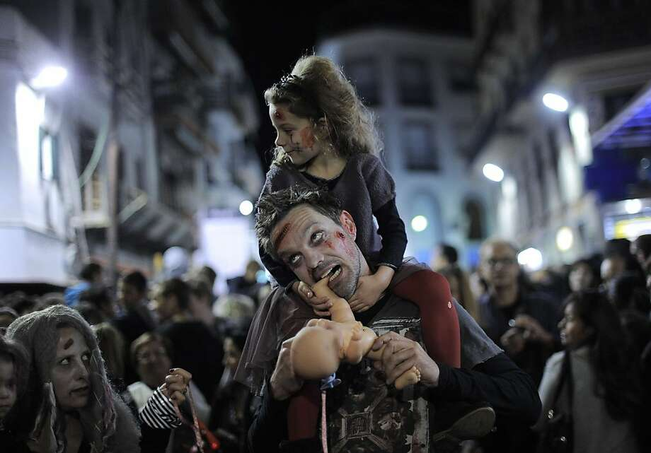 Do you want to chew on Dolly now, Hon? It's heartening to see a zombie father spending quality time with his zombie daughter in Sitges, Spain. Photo: Josep Lago, AFP/Getty Images
