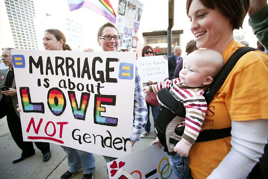 DETROIT, MI - OCTOBER 16: Kristen Vanderzouwen (R) of Grand Rapids, Michigan, her baby Alexzander, 3 months, Danielle Helgeson (C) of Allendale, Michigan and Melissa Schaub (L) of Allendale, Michigan attend a rally in favor of same-sex marriage at the U.S. Courthouse where U.S. District Judge Bernard Friedman will hold a hearing today that could overturn Michigan's ban on same-sex marriage October 16, 2013 in Detroit, Michigan. The lawsuit was brought by April DeBoer and Jayne Rowse, a gay couple who are raising three adopted children together. Michigan passed a constitutional amendment in 2004 that defined marriage as being between a man and a woman.  (Photo by Bill Pugliano/Getty Images) Photo: Bill Pugliano, Getty Images