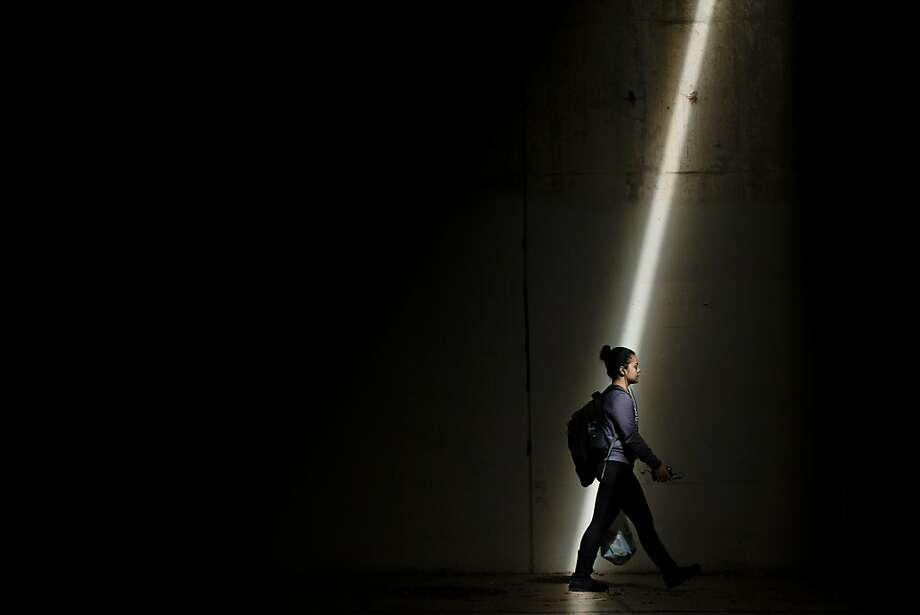 A shaft of light illuminates a pedestrian as she passes beneath Interstate 95 in Philadelphia. Photo: Matt Rourke, Associated Press