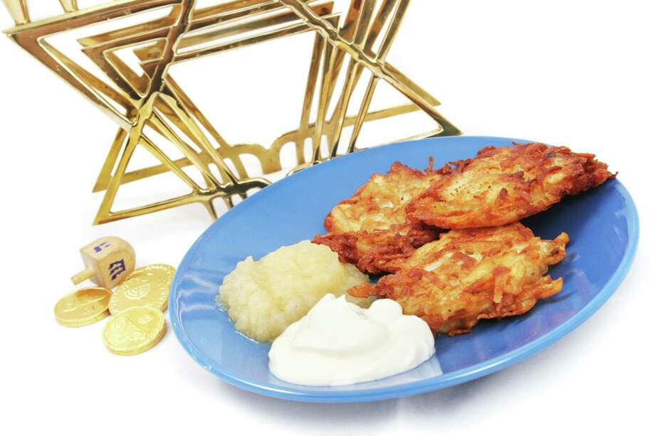 Plate of potato pancakes, a dreidel and Hanukkah gelt, and a menorah on white. Photo: Lisa F. Young / Lisa F. Young - Fotolia