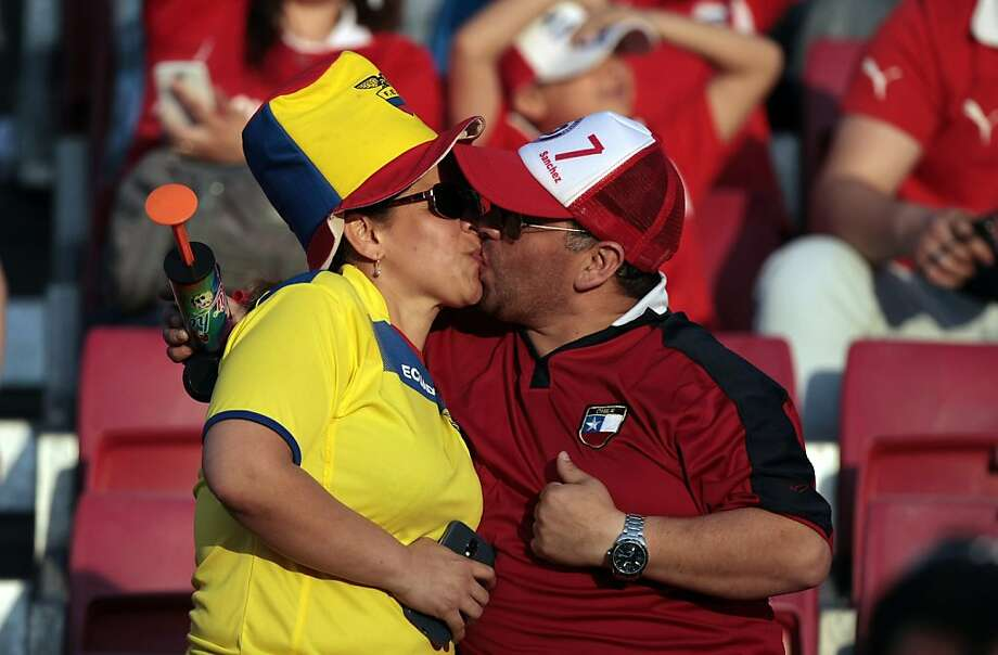Pre-game warm-up: Opposing-team football fans kiss before the 2014 World Cup qualifier between Chile and Ecuador in Santiago. Will they still be friends at the end of the match? Photo: Luis Hidalgo, Associated Press