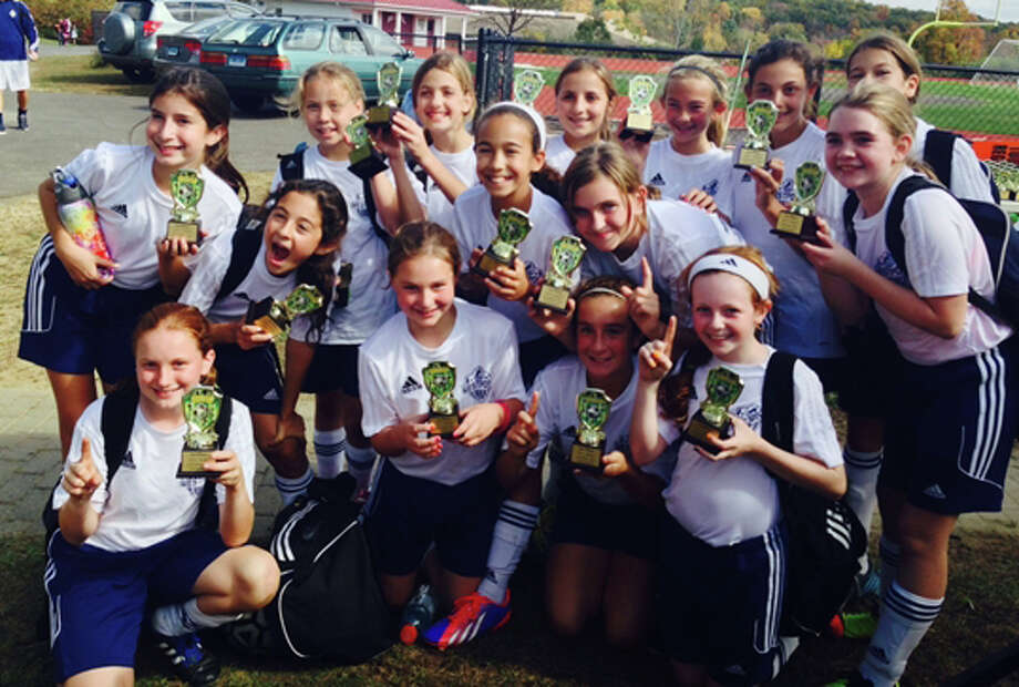 Westport's U12 girls' soccer team celebrates after finishing first in its group in a Columbus Day tournament in Bethel. Photo: Contributed Photo / Westport News