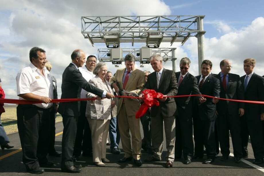 Gov. Rick Perry, center, cuts the ribbon during a ceremony for the opening of Texas 130 just west of Lockhart on Oct. 24, 2012. The toll road's builder, citing lower than expected toll collections, defaulted and handed over the tollway over to its creditors.