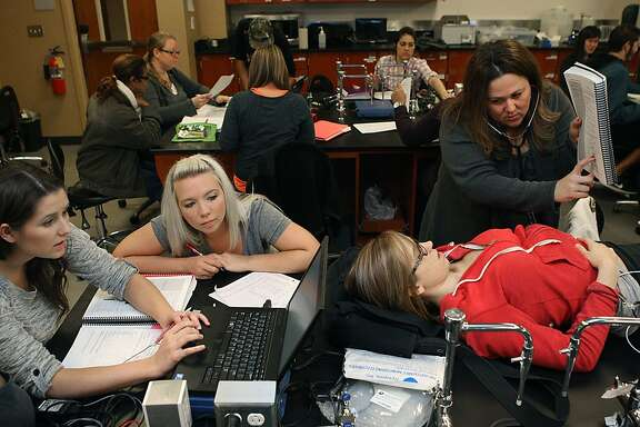 Left to right--Students Jordyn Mockovciak (on computer), 22 years old, Amanda Cyrus, 24 years old,  Christina Coyner (standing), 34 years old, and Kasara Staring (wearing red), 21 years old, work on ECG data in the human physiology course at Solano Community College in Vacaville, California, on Wednesday, October 16, 2013.  Solano College is participating in a new pilot program that will offer classes such as this during summer at a higher cost.
