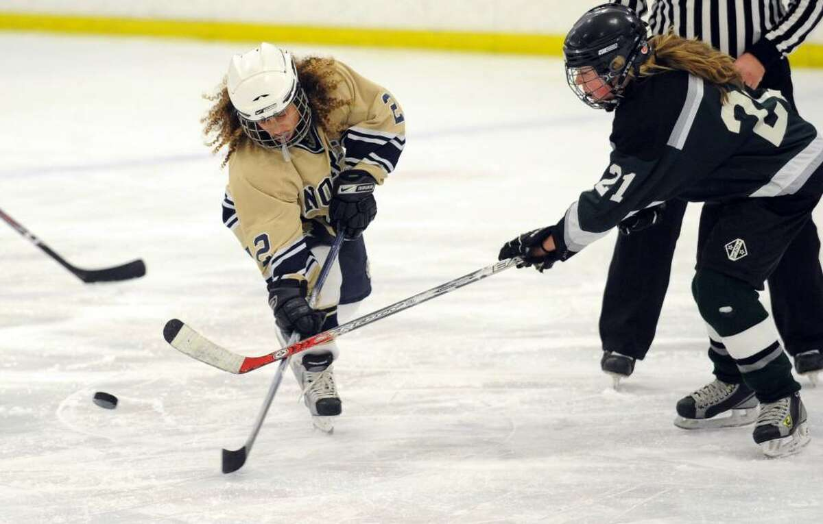 Notre Dame-Fairfield's Molly Verderame and Guilford's Megan Powell battle for the puck during Wednesday night's game at the Milford Ice Pavilion.