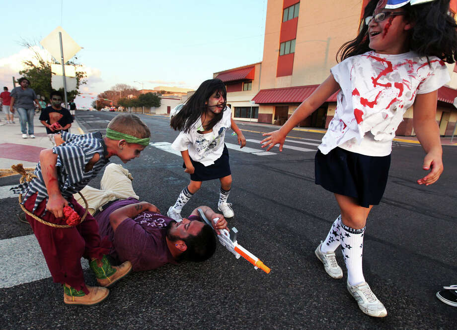 Survivor Randall Lane lays on the ground while being attacked by zombies near the end of the 2nd Annual Zombie Walk and Food Drive Saturday Oct. 12, 2013 at the Noel Plaza in Odessa, Texas.  According to Jessica Perez, one of the event organizers and a Zombie Brigade member, the point of the walk was to tie together the zombie culture with helping a charitable cause. Participants were asked to bring canned goods to be donated to the West Texas Food Bank. Rosie Simmons, a volunteer and coordinator at the food bank, stated that last year's zombie walk raised 900 pounds of food which totalled to 750 meals. (AP Photo/Odessa American, Edyta Blaszczyk) Photo: Edyta Blaszczyk | Odessa America, Associated Press / Odessa American
