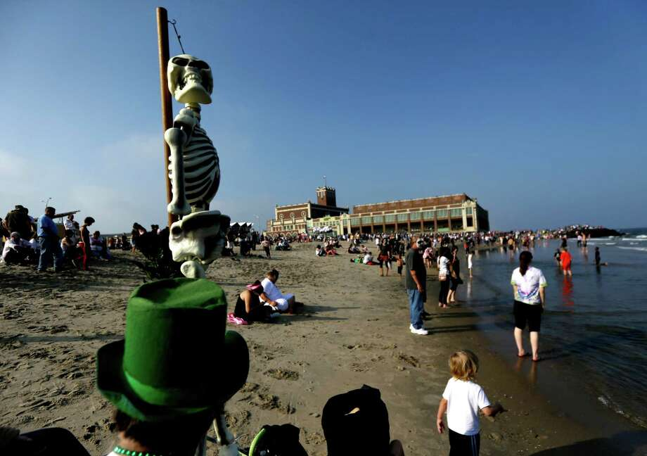 A fake skeleton is held up by a man as people dressed up as zombies hang out on the beach near the Asbury Park boardwalk, Saturday, Oct. 5, 2013, in Asbury Park, N.J. According to Guinness World Record adjudicator Michael Empric, the 9,592 zombies gathered sets a new record for largest zombie walk. (AP Photo/Julio Cortez) Photo: Julio Cortez, Associated Press / AP