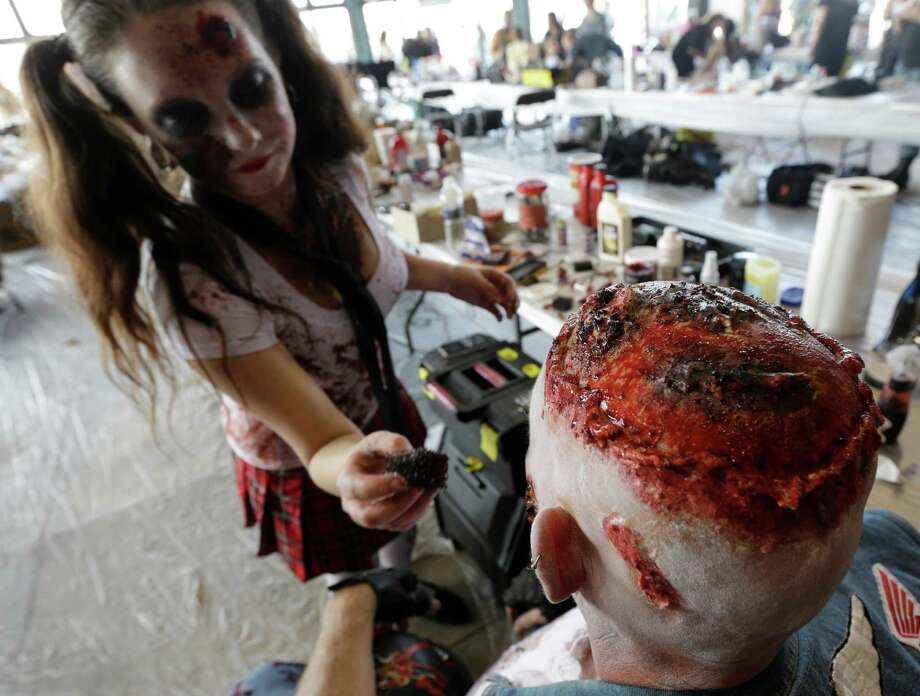 Make up artist Dena Ziemba, left, works on the makeup of Dean Dubiny, of Edison, N.J., while preparing for a zombie walk at the Asbury Park boardwalk, Saturday, Oct. 5, 2013, in Asbury Park, N.J. According to Guinness World Record adjudicator Michael Empric, the 9,592 zombies gathered sets a new record for largest zombie walk. (AP Photo/Julio Cortez) Photo: Julio Cortez, Associated Press / AP
