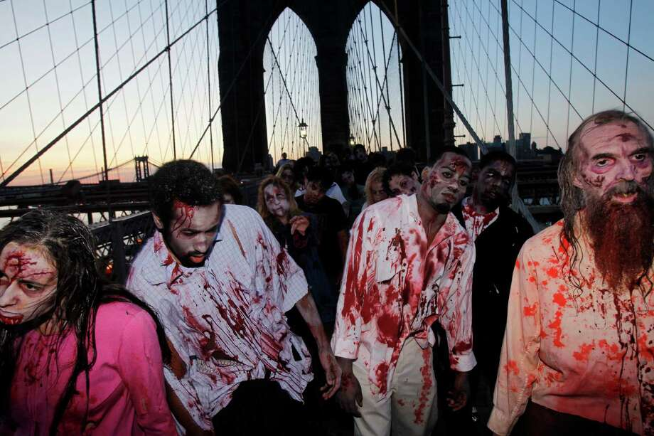 "FILE - Costumed actors, promoting the Halloween premiere of the AMC television series ""The Walking Dead"", shamble along the Brooklyn Bridge while posing for pictures in New York, in this Oct. 26, 2010 file photo. Clemson University English professor Sarah Lauro says people are more interested in zombies when they're dissatisfied with society as a whole. As of last year, Lauro said, zombie walks had been documented in 20 countries. The largest gathering drew more than 4,000 participants at the New Jersey Zombie Walk in Asbury Park, N.J., in October 2010, according to the Guinness World Records. (AP Photo/Seth Wenig, File) Photo: Seth Wenig, Associated Press / AP"