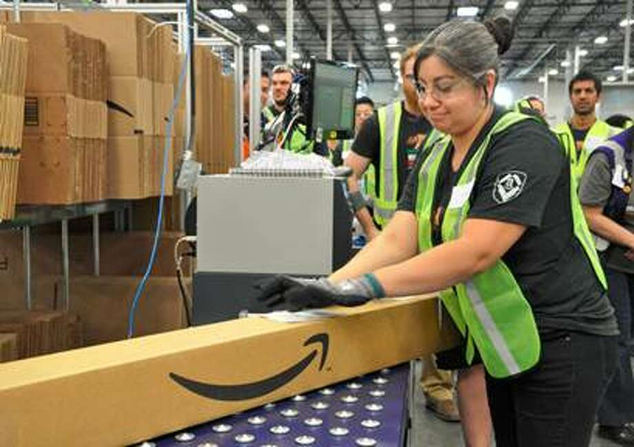 Workers at Amazon's Schertz fulfillment center ready orders during the first day of shipping operations at the center.