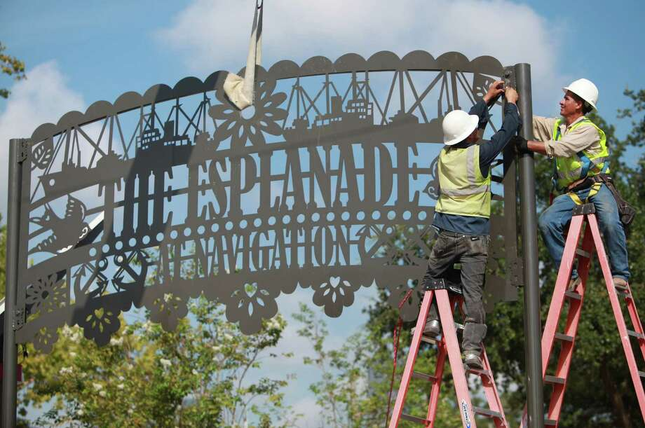 Rosendo Fabela and Irineo Zamora secure the street art in the entrance of the Navigation Boulevard Esplanade, the site of the East End Street Fest. Photo: Mayra Beltran, Staff / © 2013 Houston Chronicle