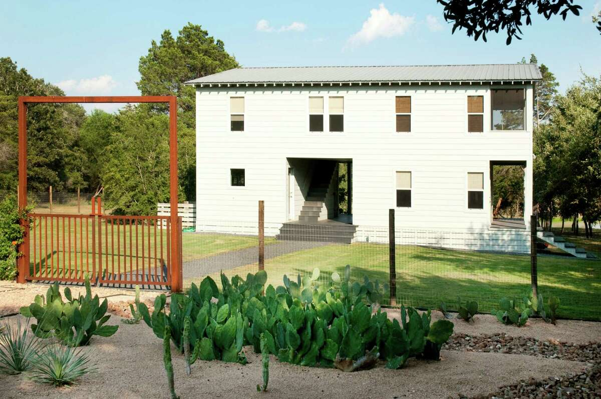 Leslie Elkins designed the main house, scaling it modestly to sit lightly on the land. Neal has landscaped open areas out front with a cactus garden and oak trees.