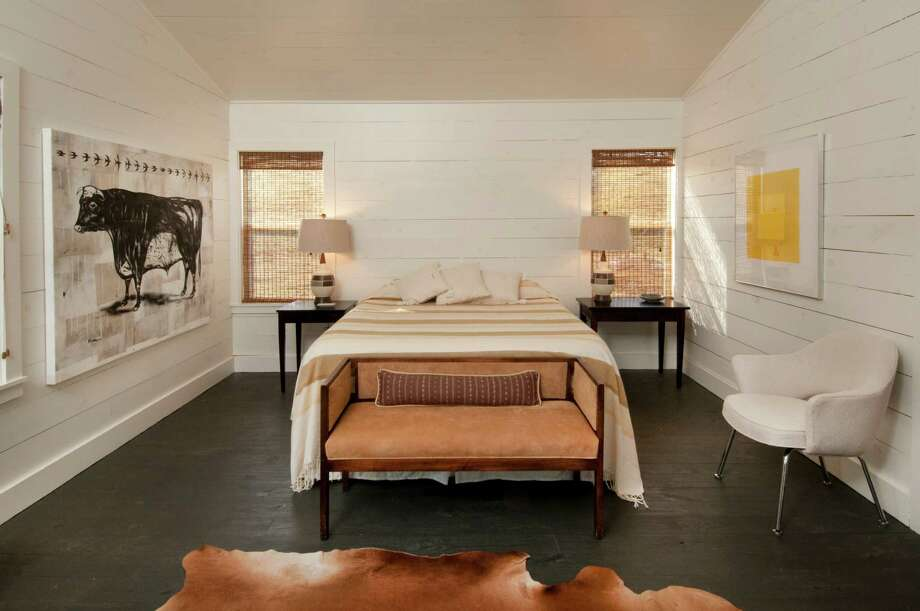 At Chad Neal's home near Shelby, a hide rug, mid-century bench recovered in suede, mid-century lamps and a bull painting by Matt Messinger make the master bedroom interesting without being fussy. Photo: Don Glentzer / ONLINE_YES