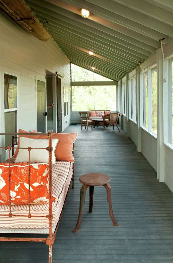Chad Neal didn't want a cookie-cutter mansion for his weekend getaway, so instead he built this cool home on a 20-acre spread near Shelby.  A pirogue that belonged to Neal's grandfather hangs above a colorful daybed on the second-story sleeping porch, which also has inviting sitting areas. Photo: Don Glentzer / ONLINE_YES