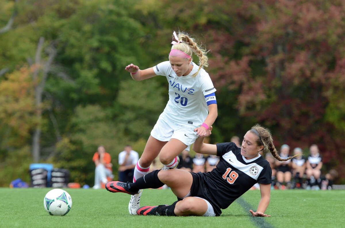 Ridgefield's Alyssa Bonnanno (15) slide tackles the ball away from Darien's Kelly Karczewski (20) during the girls soccer game at Darien High School on Wednesday, Oct. 16, 2013.