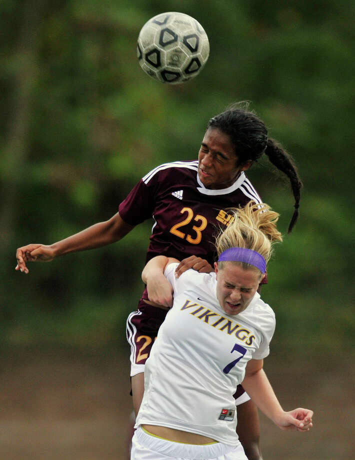 St. Joseph's Leah Lewis leaps over Westhill's Rachel Benz to get a head on the ball during their game at Westhill High School in Stamford, Conn., on Wednesday, Oct. 16, 2013. St. Joseph won, 4-1. Photo: Jason Rearick / Stamford Advocate