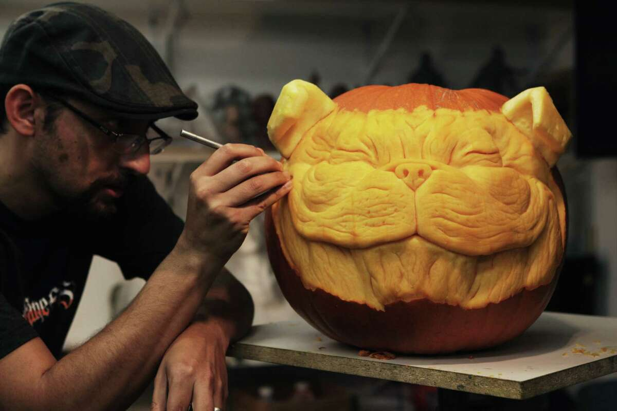 Alfred Paredes puts the finishing touches on a 3-D pumpkin sculpture for Halloween.