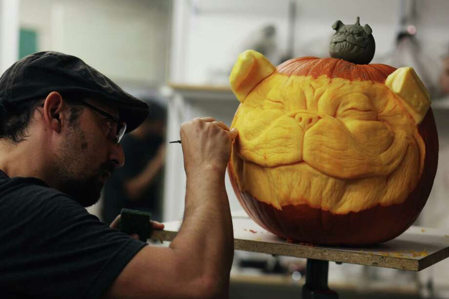 Alfred Paredes puts the finishing touches on a 3D pumpkin sculpture for Halloween. Photo: --