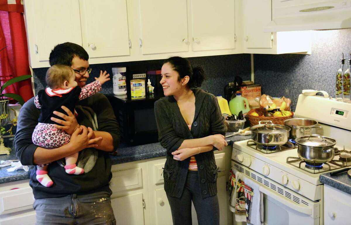 Julio Rodriguez and his girlfriend Stephanie Rodriguez cook in the kitchen with their 8-month-old daughter, Juliana, in their Danbury, Conn. home on Wednesday, Oct. 16, 2013. They live with the father's family and Stephanie receives federal grants from the Special Supplemental Nutrition Program for Women, Infants and Children (WIC) to help pay for food for herself and her child. Because of the government shutdown, however, there is only about two weeks of funding left to keep the WIC program going unless the shutdown ends.