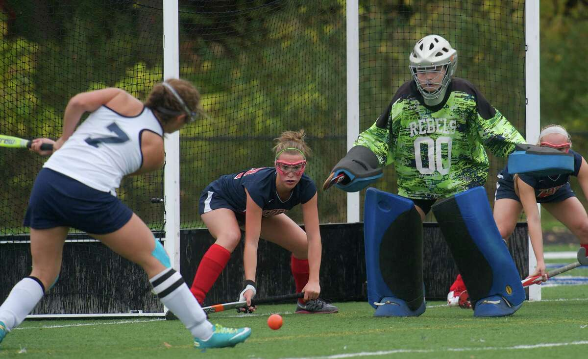 Immaculate's Sara Rizzo, 7, takes a shot on goal as New Fairfield's Jenna Joyal, 12, and goalie Sam Farrell defend during a girls field hockey game between New Fairfield High School and Immaculate High School in Danbury, Conn, on Wednesday, October 16, 2013.
