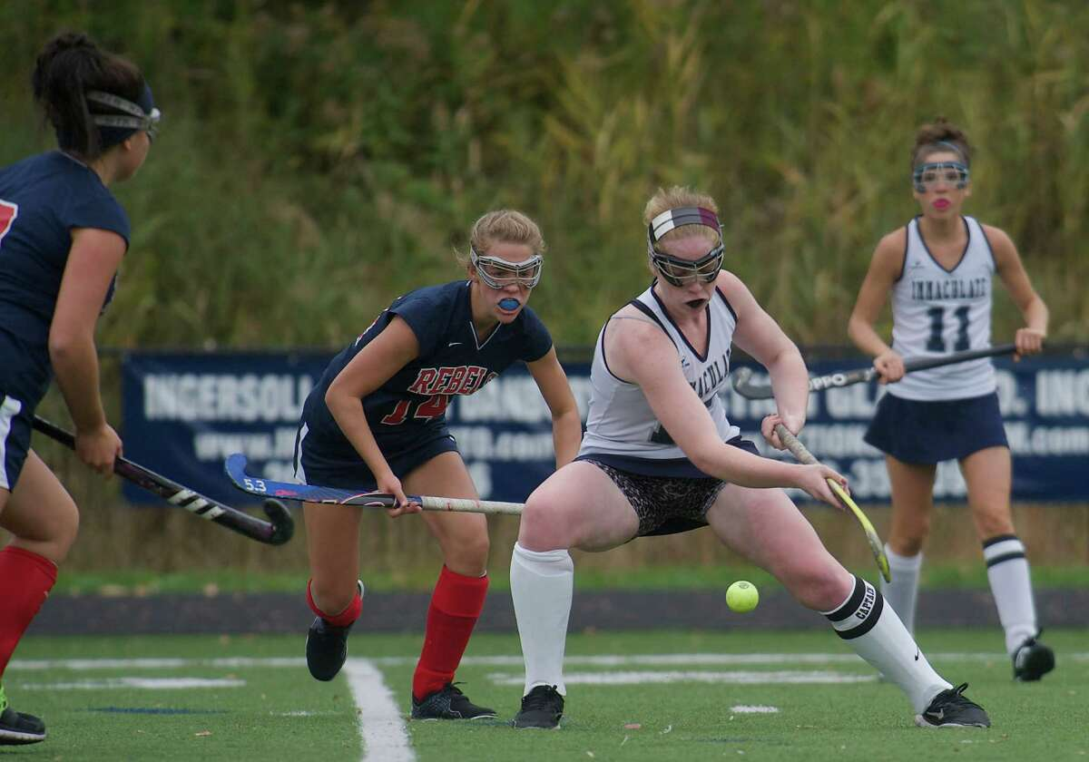 Immaculate's Meredith Keenan, 12, tries to move the ball upfield as New Fairfield's Nicole Hughes, 14, and Steph Nell, 3, move in. Immaculate's Amanda Loya, 11, looks on during a girls field hockey game between New Fairfield High School and Immaculate High School in Danbury, Conn, on Wednesday, October 16, 2013.