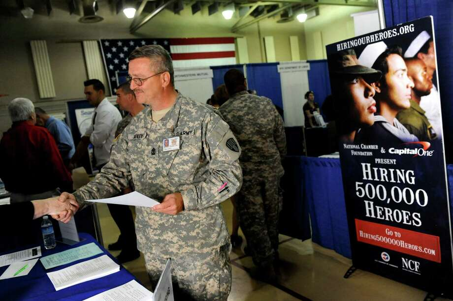 First Sgt. Gary Ashley, center, receives information on jobs with the U.S. Postal Service during the Hiring Our Heroes job fair on Wednesday, Oct. 16, 2013, at the New York Division of Naval & Military Affairs in Latham, N.Y. (Cindy Schultz / Times Union) Photo: Cindy Schultz / 00024274A