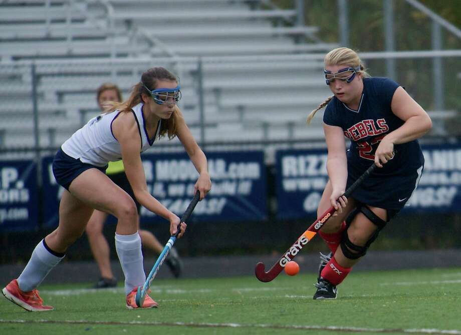 Immaculate's Nicole Demelo, 4, and New Fairfield's Lizze Murlagh, 23, during a girls field hockey game between New Fairfield High School and Immaculate High School in Danbury, Conn, on Wednesday, October 16, 2013. Photo: H John Voorhees III / The News-Times Freelance